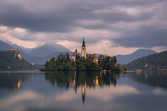 Lake Bled (ludwigriml) Tags: bled blue bluehour calmness castle churchtower cliff clouds evening forest hills island lakebled lights mountainrange reflections rock serenity silence sky slovenia tower twilight water calmwaters church fog lake mountains