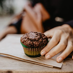 A girl's hand holding a chocolate cupcake. thumbnail