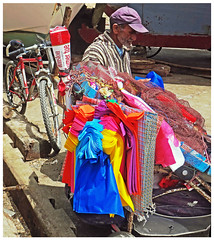 Sidewalk sales - Essaouira, Morocco (TravelsWithDan) Tags: candid colors sidewalksales man city urban ourdoors street bicycle cigarets bags sellingonthestreet baseballhat morocco essaouira africa hot canong3x