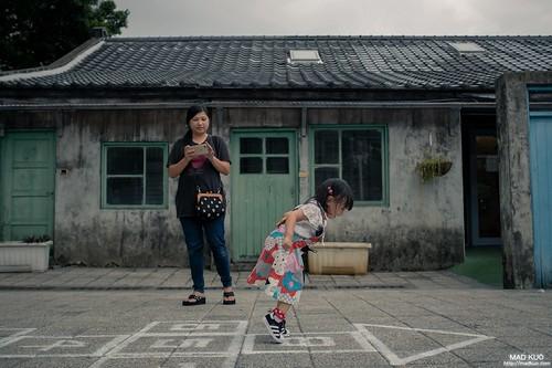 在我那彩色電視的童年已很少人在玩跳房子了(三字經鬼抓人比較流行),如今,智慧手機的年代應該更少小朋友會玩了。照片中的小女孩也是媽媽在一旁教學。