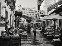 (GLKPhotos) Tags: street streetlife people relaxing albuferia streetsigns bars cafes buildings structures sunnyday tonalcontrast contrast awnings tables chairs blackandwhite mono monochrome candid primelens 50mm niftyfifty panasonicgx8 oldtown balconies windows dark seating cobbledstreet shaded shadow squares portugal
