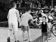 Deal! (Janka Takács Sipos) Tags: bystander calle candid city documentary flâneur photo photography public rue space strada stranger strasenfotografie street streetphoto streetphotographer streetphotography streets streetscape ulica unposed urban urbanphoto urbanphotography utcafotó улица רחוב vietnam vietnamese asia asian hanoi boy boys square smile child children kid play bnw black white blackandwhite monochrome fuji fujifilm xseries x20 bike bicycle motorbike motorcycle park bush hedge shorts barefoot brat