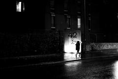 In front of the lit entrance (pascalcolin1) Tags: paris13 femme woman nuit night pluie rain parapluie umbrella lumière light reflets reflection porte door photoderue streetview urbanarte noiretblanc blackandwhite photopascalcolin canon canon50mm 50mm