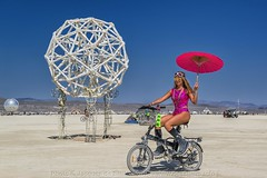 Red Biking Beauty – j8e_19265-63-ps1 (Jacques de Selliers (OFF/ON)) Tags: bike biker red redbiker umbrella redumbrella burningman2018 burningman blackrockcity deselliers jacquesdeselliers beauties burningmanbeauties nicewomen beautifulwomen sparklepony sparkleponies sexywoman burners burningmanart art playaart contemporaryart