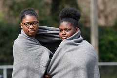 A'Nasia Monford shares a blanket with her teammate at the track and field meet.