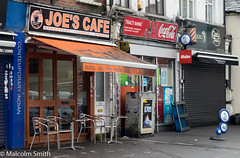 Joe & Tracy Anne (M C Smith) Tags: newsagent hertfordshire cafe pentax k3 reflections chairs tables pavement signs letters symbols numbers black bag waste red orange blue shutters shops pallet chrome