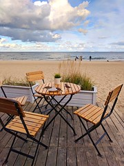 A quaint little cafe by the shore. (elnina999) Tags: sopot poland resort spa cafe roundtable frenchbistro sunny sand outdoors relaxing elegance deck view gdanskbay shore horizon pixelphone mobilephotography birds dishes crumbs greatday holiday