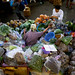 Woman surrounded by vegetables in her market stall in Warorot Market in Chiang Mai, Thailand