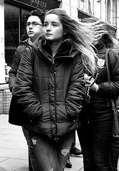 Breeze (Owen J Fitzpatrick) Tags: ojf people photography nikon fitzpatrick owen pretty pavement chasing d3100 ireland editorial use only ojfitzpatrick eire dublin republic city tamron candid joe candidphotography candidphoto unposed natural attractive beauty beautiful woman female lady j along bw black white mono blackwhite blackandwhite monochrome blancoynegro pretoebranco photoshoot street st saint patricks day holiday festival blonde hair breeze wind coat yankees face visage zip sinnotts king south pub public house outside portrait