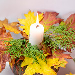 Burning candle in original candlestick with pumpkin and autumn leaves thumbnail
