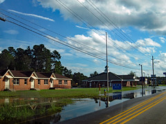 Flooding On Kahn Drive. (dccradio) Tags: lumberton nc northcarolina robesoncounty outdoor outdoors outside sky clouds bluesky powerpole utilitypole electricpole pole streetlight lamppost lightpole yellowlines road street kahndrive grass lawn greenery yard ground water flood flooding hurricaneflorence florence hurricane hurricaneaftermath stormaftermath reflection waterreflection utilitywires utilitylines electricwires electriclines lumbeeriverelectric building architecture paved pavement standingwater floodwaters sign words text canon powershot a3400is september afternoon monday earlyfall earlyautumn latesummer accessroad cloud firehydrant hydrant