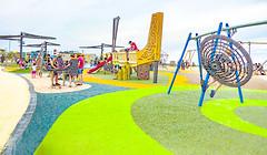 Playing Around (Steve Taylor (Photography)) Tags: playground boat swing slide design digitalart park highkey green gold yellow white blue children people newzealand nz southisland canterbury christchurch newbrighton