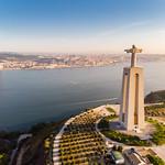 Luftaufnahme der Cristo Rei Statue von hinten mit Ponte 25 de abril Brücke in Almada Lissabon thumbnail