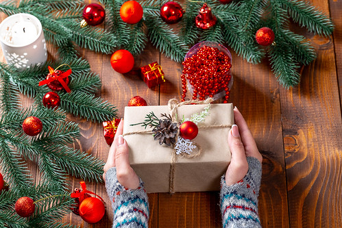 Christmas gift in women's hands with Christmas decor