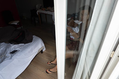 Young woman in hotel room in Paris (kateafter) Tags: woman paris hotel reflection daylight france parisfrance onewomanonly newlife loneliness onegirlonly oneperson people photography spirituality vertical window balcony lookingatview silhouette indoors lifestyles youngadult sitting casualclothing curtain bedfurniture bedding bedroom brownhair females focusonshadow homeinterior horizontal humanbodypart humanface humanhair humanhand humanmouth shadow sheetbedding youngwomen suitcase hotelroom motel arrival bag blackandwhite travel tourist women luxuryhotel blackcolor colorimage image apartment leg limb