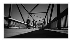 Entering Space (VanveenJF) Tags: bridge edmonton fujifilm samyang wideangle alberta xt10 film bw black white border canada kanada canadian people walking ghost steel hard cold graphic crossingrivernorthsaskatchewan