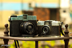 Aging Together (shamahzoha) Tags: cameras two pair black blue silver macro bokeh shelf dusty old aged vintage colors colorful vibrant beauty beautiful tech technology gadget evolution film lens simple minimal