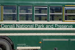 AUGUST 1 2018 - Denali Alaska: Close up detail view of the green tour shuttle bus in Denali National Park in Alaska. The road is closed to personal vehicles. Tourists must ride a bus (m01229) Tags: alaska autumn ak gravel color american alpine nature dangerous denali dusty brown fall shuttle summer national road peak curve transportation bus outdoors landscape sky lake sightseeing nationalpark mountains tundra driving vacation travel wild clouds scenic remote denalinationalpark adventure northamerica wildlife highway cloud landscapes united tour park usa tourism wilderness mountain