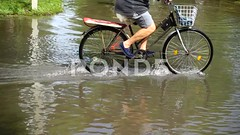 Flood in the city after a rain. The man by bicycle moves down the street.Slow motion. (daria.boteva) Tags: bicycle bike man rain splash water tire road puddle city street flood weather spray adventure danger hazardous machine motion moving mud splashing storm thunderstorm transportation vehicle warning wave accident climate disaster dramatic ecology environment nature raindrop rainfall rainwater season tornado trouble transport highway slow rainy