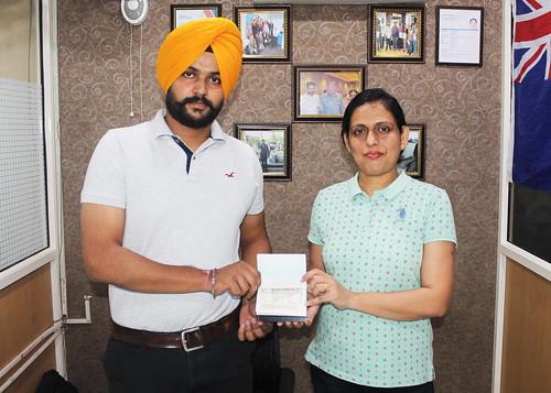 Ms. Parwinder Kaur (Director of West Highlander) handing over Canada Open Work Visa to Harsimrat Singh