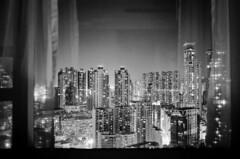 Through the Window at Night. (Bill Thoo) Tags: hongkong 香港 mongkok 旺角 throughthewindowatnight window night longexposure city cityscape urban travel landscape buildings architecture built highrise apartments skyscrapers citylights film analog analogue filmphotography filmcamera analogphotography analoguephotography monochrome bnw blackenedwhite blackandwhite blackandwhitefilm blackandwhitefilmphotography 35mm 35mmfilm 35mmfilmphotography 35mmfilmcamera lecia m4 leicam4 voigtlander voigtlandercolorskoparpii3525 3525 kodak tmax kodaktmax kodaktmax400 push2 pushed2 push2stops pushed2stops
