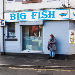 Dewsbury 001 (Peter.Bartlett) Tags: square fastfood unitedkingdom wall people urban city olympuspenf woman drainpipe westyorkshire cellphone urbanarte peterbartlett doubleyellowlines girl streetphotography candid uk m43 microfourthirds mobilephone shopwindow standing sign lunaphoto poster facade dewsbury england gb