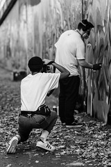Shoot The Artist (Sean Batten) Tags: blackandwhite london england unitedkingdom gb bw streetphotography street candid people graffiti city urban eastlondon leaves wall artist photographer nikon d800 70200