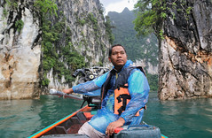 Our boatman maneuver through the huge limestone mountains (B℮n) Tags: thailand three rocks karst formations landmark เขาสก khao sok national park jungle oerbos wildlife south wild mammals mountains virgin oldest forest rainforest sandstone limestone mountain 950m monsoon rain erosion asian elephant tiger sambar deer bear guar banteng serow boar pigtailed macaque langur white handed gibbons squirrel boat man trip lake klong long cheow lan clouds magic phutawan raft house resort kayak kayaking explore adventure greathornbill twilight boatman engine automotive longtailboat longtail 50faves topf50