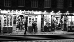 tourists browsing after dark 01 (byronv2) Tags: royalmile edinburgh edinburghbynight edimbourg street candid peoplewatching night nuit nacht cashmere shop shopping pavement tourists buying oldtown blackandwhite blackwhite bw monochrome