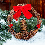 Wreath with a red bow, cones and branches on a snow background. The concept of the traditional symbol of the Christmas holidays thumbnail