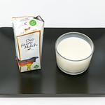 Die faire Milch - Gentechnikfreie - Deutsche Vollmilch im Glas und Verpackung auf schwarzem Teller thumbnail