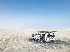 Ruined SUV somewhere in desert (Pavel's Snapshots) Tags: tour surface flat suv car vehicle abandoned ruined desert sand sky day qatar middleeast toyota safari landscape phone iphone mobile vivid filter rust forgotten burnt travel trail haze evening wasteland blue