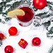 Glass Cup with mulled wine on Christmas background with toys and presents on snow