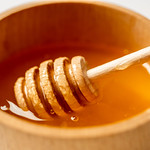 Natural bee honey in a wooden bowl on a white background thumbnail
