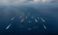 USS Ronald Reagan (CVN 76) and S Hyuga (DDH 181), right, sail in formation with 16 other ships.