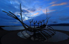Sun Voyager into the Night (Eye of Brice Retailleau) Tags: angle beauty composition landscape outdoor paysage perspective scenery scenic view extérieur cloud clouds cloudy cloudscape nuages backback backpacking travel traveling sky skyscape outside outdoors roadtrip europe islande iceland ciel coucher de soleil panorama sea ocean seaside oceanside coast dusk sun light sunset art statue boat voyager reykjavik blue hour