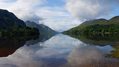 The still waters of Loch Shiel (WISEBUYS21) Tags: bonnie prince charlie charles edward stuart jacobite 45 landscape still water mountain range reflection reflections harry potter glenfinnan blue sky white clouds green trees forest remote wilderness mike tomkies lake loch lakeside shoreline pebbles gravel small stones wisebuys21 best favourite faves scotland panorama positive rate sony deep tranquil