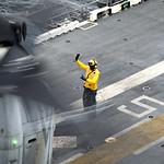 A Sailor directs an MV-22 Osprey during flight operations. thumbnail