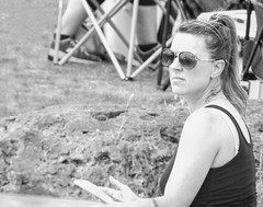 Tablet Reader (clarkcg photography) Tags: blackandwhite bw blackwhite candid park reading reader tabletreader woman sunglasses reflection earrings ponytail hair