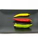 Drei kleine bunte Chilischoten in geld, rot und grün auf einem schwarzen Teller
