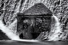 At the bottom of the dam (David Feuerhelm) Tags: monochrome bw blackandwhite noiretblanc schwarzundweiss negroyblanco nikkor contrast motion blur water slowshutter dam blocks building nikon d90 70300mmf4556