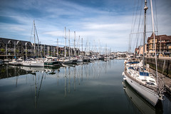 """yachts lined along the quays, summer reflections, Marina of Port Deauville, Boulevard Eugene Cornuch, Deauville, """"Côte Fleurie"""", Calvados, Normandy, Normandie, France (grumpybaldprof) Tags: deauville """"côtefleurie"""" calvados normandy normandie france horses racing """"racecourses"""" casinos hotels seaside resort port yachts """"parisianriviera"""" fashionhighsociety proust """"insearchoflosttime"""" fashionable """"portdeauville"""" """"boulevardeugenecornuch"""" marina reflections water boats wetreflections quays striking artistic interpretation impressionist stylistic style contrast shadow bright dark black white illuminated colour colours colourful canon 70d """"canon70d"""" sigma 1020 1020mm f456 """"sigma1020mmf456dchsm"""" """"wideangle"""" ultrawide"""