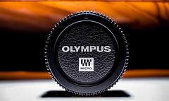 Body cap, Olympus. (CWhatPhotos) Tags: cwhatphotos camera photographs photograph pics pictures pic picture image images foto fotos photography artistic that have which contain bodycap body cap black micro four thirds olympus macro closeup 30mm em10 mk lll plastic 43 rds 43rds light shadow art round circle circular graphic bw logo cover burning orange background vision approach view