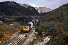 Off the beaten track. 47292 passes the waste china clay tips near Restowrack on the Parkandillack branch with a Speedlink from Severn Tunnel Junction. 2April1986. (mikul44171) Tags: 47292 moonscape slag wasteheaps claycountry speedlink restowrack chinaclay ferrywagon