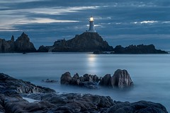 Stillness In Blue (Andy Bracey -) Tags: andybracey bracey jersey channelislands longexposure coast coastal stillness stillnessinblue rocks water sea milkywaters lighthouse lacorbiere lightson summer holidays evening