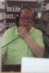 Carpenter answers the telephone as he works in the pharmacy, located in the back part of the store.