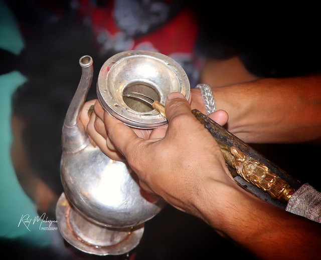 Fetching alcohol comming out from the god Sweat Bhairab for offering Ganesh.