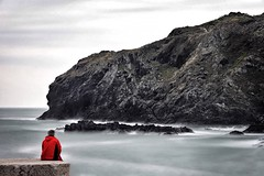 Long exposure of lonely man in front of sea. (BadGunman) Tags: shoreline southoffrance france pyrénéesorientales wave mist rocks cloudy white grey mediterranée sea water solitaire alone homme man thought red orange badweather hill colline falaise cliff port portvendres canon longexposure