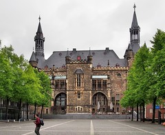 Aachener Rathaus (Town Hall) and Katschhof public square, Aachen, Nordrhein-Westfalen, Germany (edk7) Tags: olympuspenliteepl5 edk7 2015 germany deutschland northrhinewestphalia nordrheinwestfalen aachen katschhof publicsquare aachenerrathaus aachentownhall 14th19thc front entrance stonecarving sculpture architecture building oldstructure unescoworldheritagesite arch window stone ashlar baywindow tower pavement tree person male crenelation crenelations