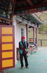 Mongolian Man In Red Hat (peterkelly) Tags: digital canon 6d gadventures transmongolianadventure asia mongolia gercamp aryapalameditationinitiationcenter buddhist temple man red hat door column pillar ter tereljmountains tereljnationalpark buddhism